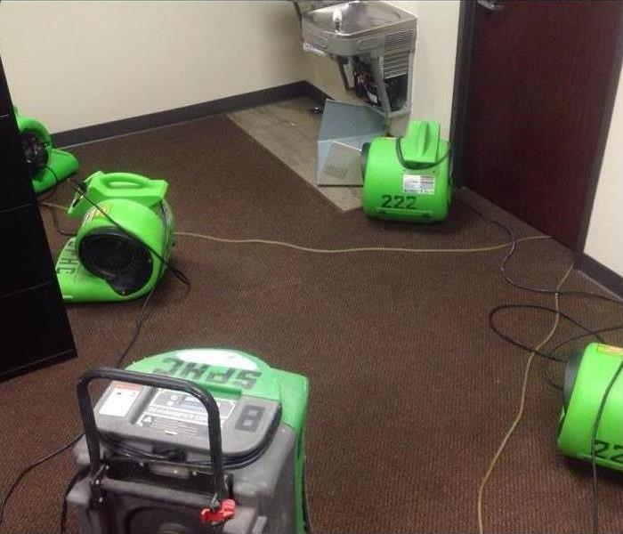 servpro green drying equipment on a wet carpet