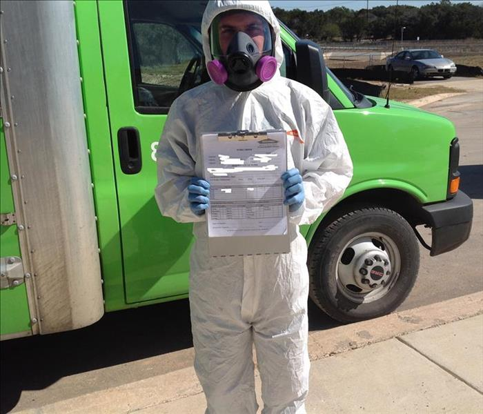Man in hazmat suit holding up a mold certification